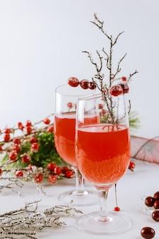 Getränk aus preiselbeeren in glas mit roter beerendekoration auf weißem hintergrund.