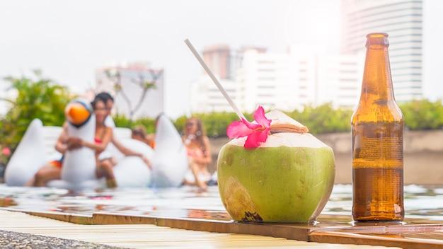 Getränk und kokosnusssaft mit flasche bier auf pool