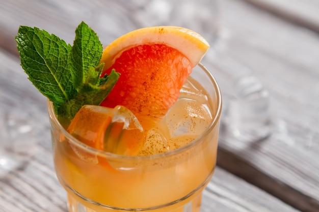 Getränk von oranger farbe. stück grapefruit und eis. frischer saft und zimt. frischen sie ihren sommer auf.