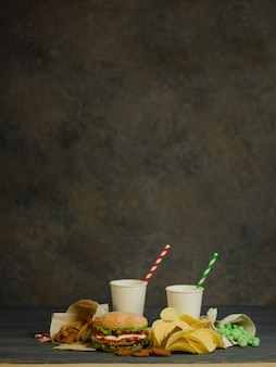 Getränke in einem pappbecher mit papiertube und hamburger, salzige snacks, brezeln, pommes.