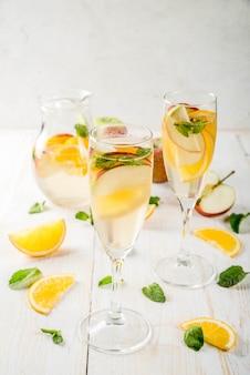 Getränke und cocktails. weiße herbstsangria mit äpfeln, orange, minze und weißwein. in gläsern für champagner, in einem krug, auf einem weißen holztisch. kopieren sie platz