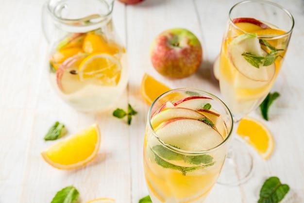 Getränke und cocktails. weiße herbstsangria mit äpfeln, orange, minze und weißwein
