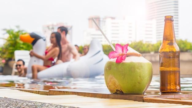 Getränke- und kokosnusssaftgetränk mit einer flasche bier im pool.