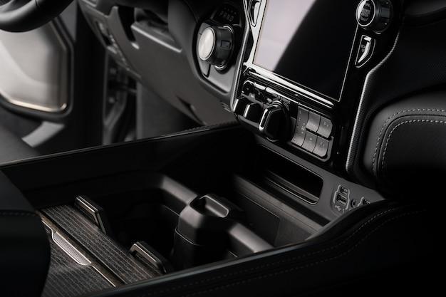 Getränkehalter hautnah in einem schwarzen luxusauto, touchscreen-systemdisplay