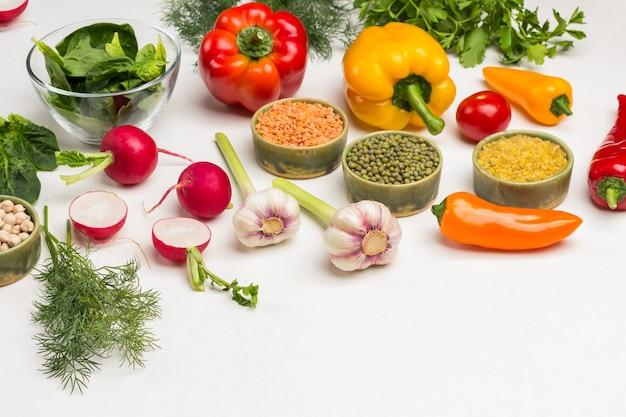 Getreide, gemüse und grüns auf dem tisch. püree, linsen, bulgur in schalen. radieschenhälften, knoblauch und farbige paprika. weißer hintergrund. ansicht von oben. platz kopieren