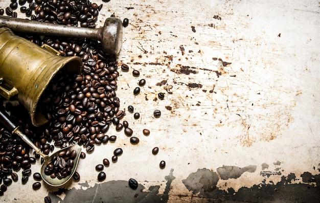 Getreide gerösteter kaffee in einem mörser mit stößel. auf rustikalem hintergrund.