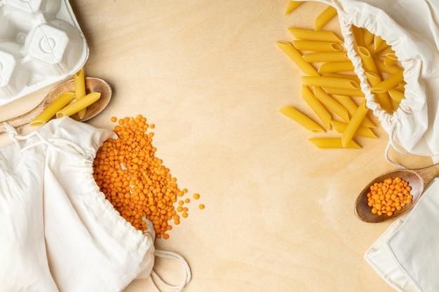 Getreide in öko-baumwollbeuteln und holzlöffeln auf holztisch. linsen, eier und nudeln im öko-paket. einkaufskonzept ohne abfall. kein plastik mehr.
