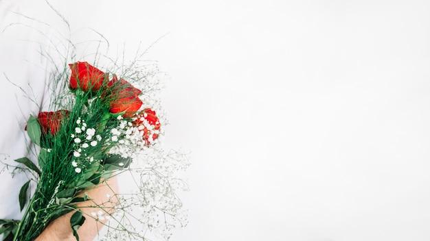 Getreide mann, der blumenstrauß von rosen hält