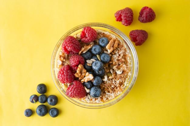 Getreide mit früchten, beeren zum frühstück. gesundes frühstück, gelber hintergrund.