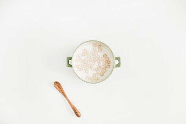 Getreide mit milch auf weiß. flache lage, draufsicht.