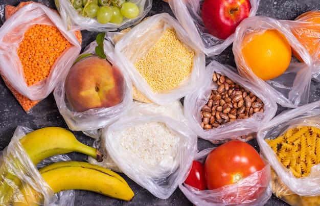 Getreide, obst und gemüse in plastiktüten auf einem dunklen tisch