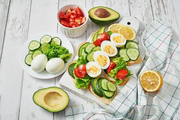 Getreidebrot-sandwiches zum frühstück mit eiern, tomaten und gurken