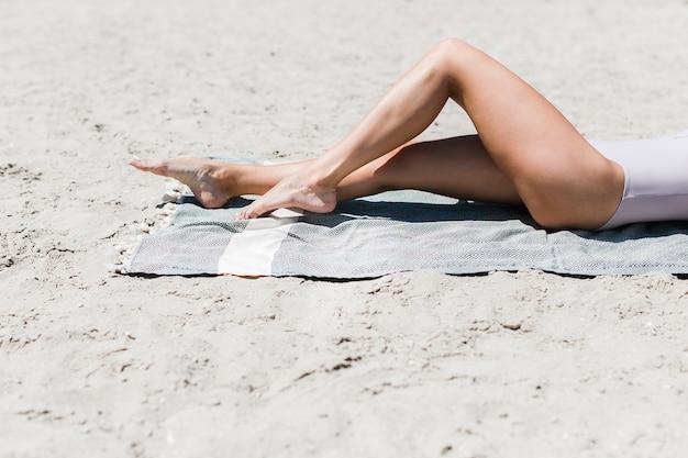 Getreidefrau, die auf stranddecke liegt