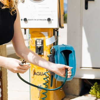Getreidefrau, die luftpumpe an der tankstelle hält