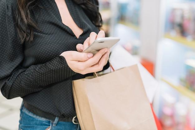 Getreidefrau mit dem smartphone, der papiertüte hält