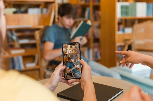 Getreidejugendliche, die foto des freunds in der bibliothek machen