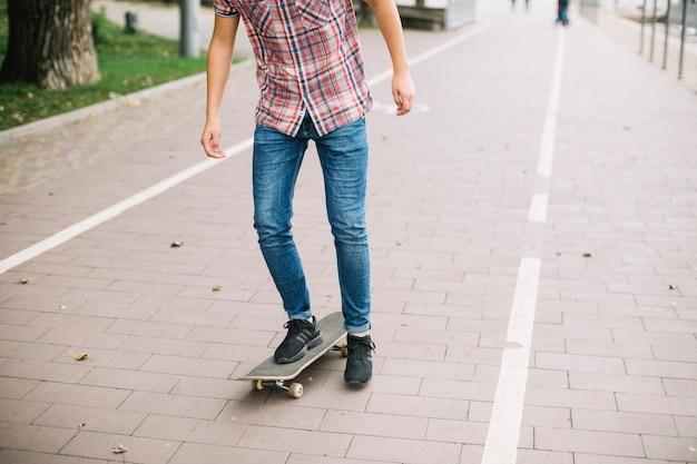 Getreidejugendlicher, der auf fahrradweg skateboard fährt