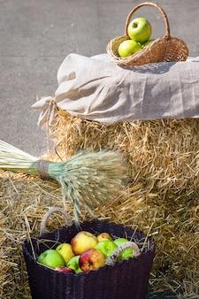 Getreideköpfe und äpfel in den körben. ernte auf dem heuhaufen