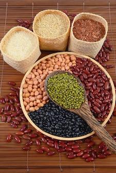 Getreidekörner und samen bohnen und weißer reis nützlich für gesundheit in den hölzernen löffeln.