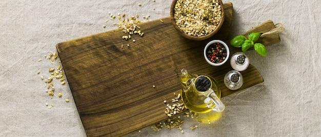 Getreidemischung in einem banner aus getreidemischung in einer holzschale auf einem schneidebrett mit olivenöl, bunten paprikaschoten und gewürzen.