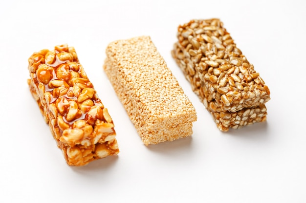 Getreidemüsliriegel mit erdnüssen, indischem sesam und samen in folge. draufsicht drei verschiedene bars, zu isolieren