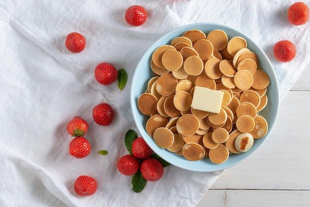 Getreidepfannkuchen in blauer schüssel mit stück butter und erdbeeren auf weiß