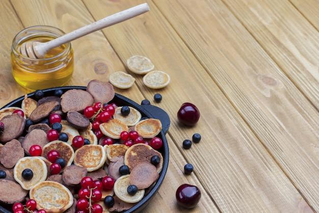 Getreidepfannkuchen und rote johannisbeeren, blaubeeren in der pfanne.