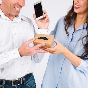 Getreidetochter, die dem vater mit smartphone geschenk gibt