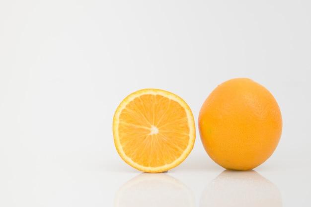 Getrennte hälfte schnitt orange und volle orange frucht auf weiß.