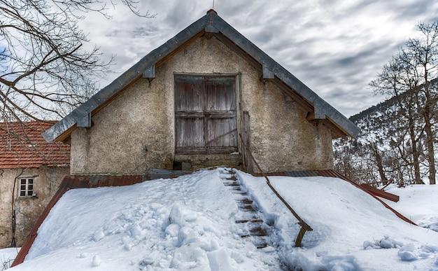 Getrenntes landhaus abgedeckt durch schnee in der winterzeit
