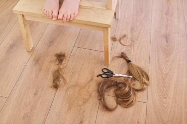 Getrimmtes haar von kindermädchen und schere auf dem boden, nackte füße des mädchens auf dem stuhl zu hause.