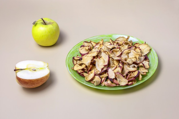 Getrocknete äpfel auf einem teller und frische äpfel