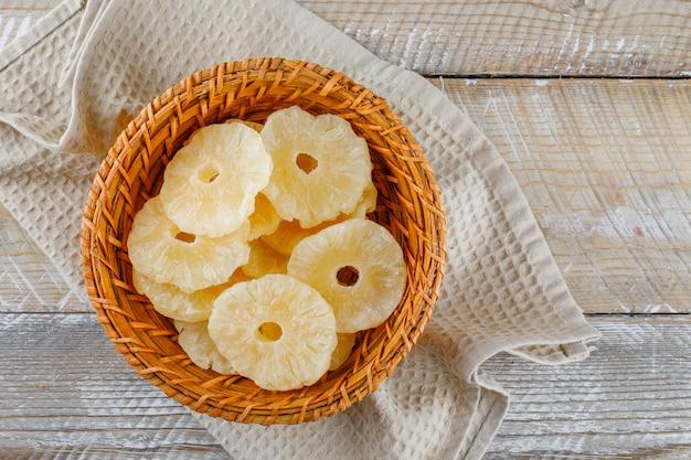 Getrocknete ananas in einem korb auf küchentuch
