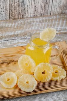 Getrocknete ananas in einem tablett mit saft auf einer holzoberfläche