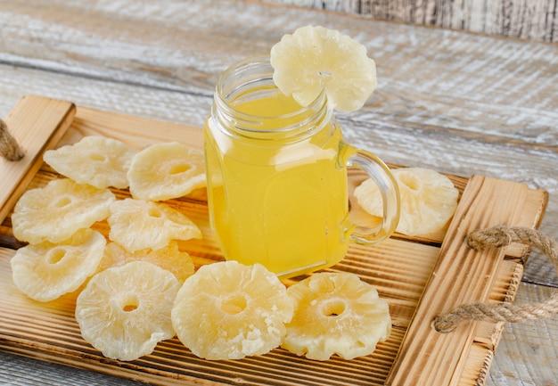 Getrocknete ananas mit saft in einem tablett auf holzoberfläche