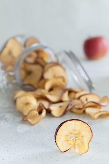 Getrocknete apfelchips im glas auf hellem holz
