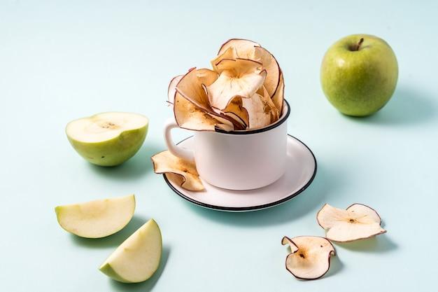 Getrocknete apfelchips in einer schale und in frischen äpfeln