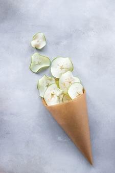 Getrocknete apfelchips in papierverpackung verpackt. gesunde snacks