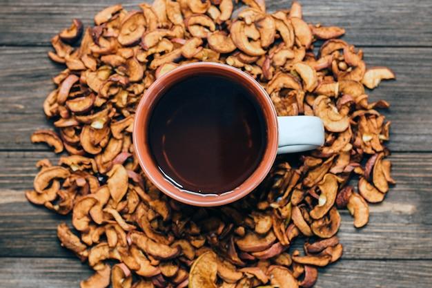 Getrocknete apfelscheiben hautnah, nützliche vitamine für getränke in einer gesunden ernährung. tasse mit uzvar.