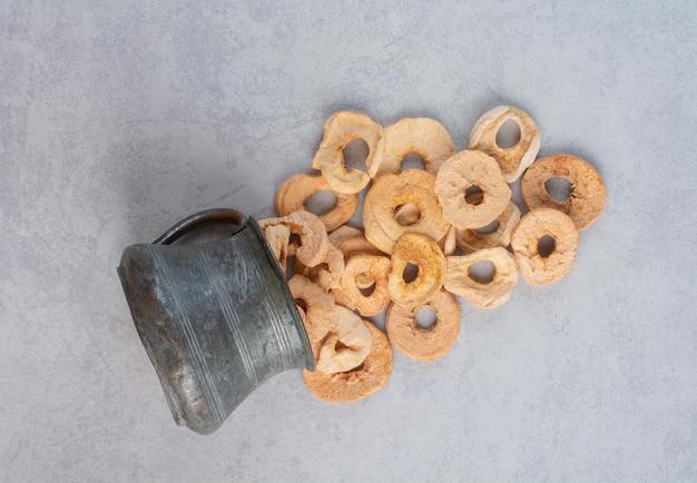 Getrocknete apfelscheiben in einem metallischen topf.