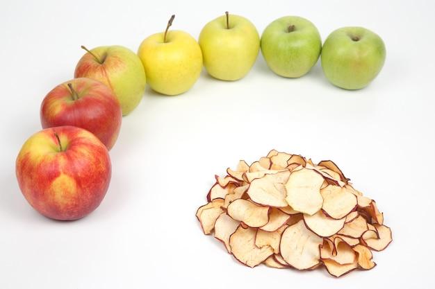 Getrocknete apfelscheiben umgeben von frischen äpfeln auf weißem hintergrund