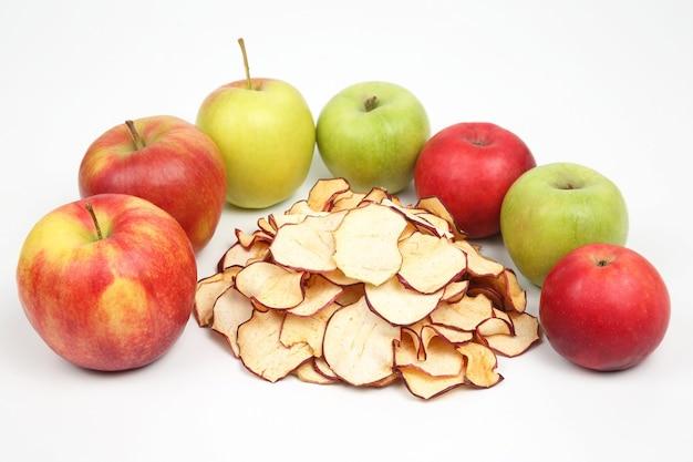 Getrocknete apfelscheiben umgeben von frischen äpfeln auf weißer oberfläche