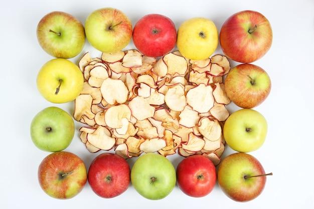 Getrocknete apfelscheiben umgeben von frischen äpfeln isoliert