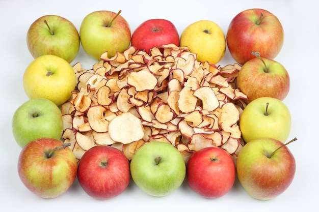 Getrocknete apfelscheiben, umgeben von frischen äpfeln