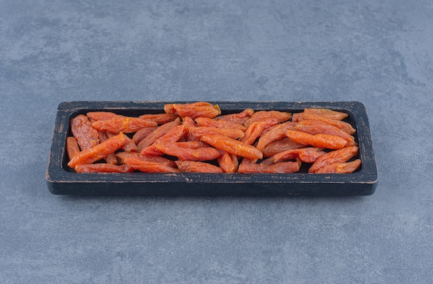 Getrocknete aprikose in der holzplatte, auf dem marmorhintergrund.