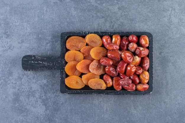 Getrocknete aprikose und oleaster auf einem brett, auf dem marmorhintergrund.