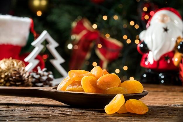 Getrocknete aprikosen in einer schüssel auf dem brett mit unscharfem weihnachtshintergrund