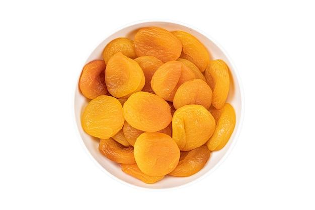 Getrocknete aprikosen in einer schüssel auf einer weißen oberfläche