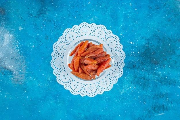 Getrocknete aprikosen in einer schüssel auf untersetzer, auf dem blauen tisch.