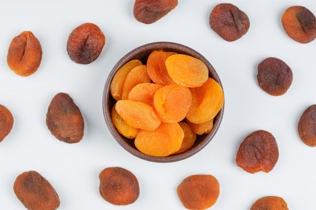Getrocknete aprikosen in einer tonschale. draufsicht.
